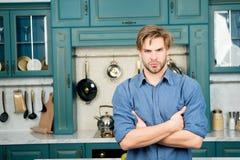 Macho mit ernstem Gesichtsstand mit den gefalteten Händen in der Küche Stockfoto
