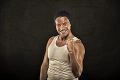 Macho na cara de sorriso com músculos fortes olhe fundo brutal, preto Homem com os braços musculares que espremem o punho firmeme imagem de stock