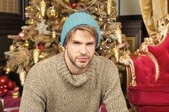 Macho no chapéu morno, camiseta sente-se na árvore de Natal imagens de stock