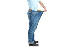 Macho que mostra seu peso perdido põr sobre calças de brim fotos de stock royalty free