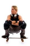 Macho que senta-se na placa do patim Foto de Stock