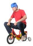 Macho sério em uma bicicleta das crianças Imagem de Stock