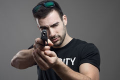 Macho security guard squinting one eye while aiming pistol at camera Royalty Free Stock Photos
