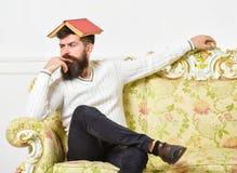 Macho si siede con il libro aperto sulla testa, come il tetto Concetto noioso della letteratura L'uomo con la barba ed i baffi si Immagine Stock