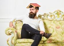 Macho si siede con il libro aperto sulla testa, come il tetto L'uomo con la barba ed i baffi si siede sul sofà, fondo bianco dell Fotografia Stock Libera da Diritti
