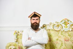 Macho sits with open book on head, like roof. Guy, teacher overdid with teaching, became crazy professor. Man with beard. And mustache sits on sofa, white wall stock photography