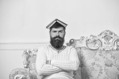 Macho sits with open book on head, like roof. Guy, teacher overdid with teaching, became crazy professor. Man with beard. And mustache sits on sofa, white wall royalty free stock photos