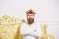 Macho sits with open book on head, like roof. Guy, teacher overdid with teaching, became crazy professor. Man with beard. And mustache sits on sofa, white wall royalty free stock image