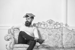 Macho sits with open book on head, like roof. Guy, teacher overdid with teaching, became crazy professor. Overwork. Concept. Man with beard and mustache sits on royalty free stock photo