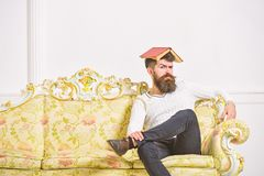 Macho sits with open book on head, like roof. Guy, teacher overdid with teaching, became crazy professor. Overwork. Concept. Man with beard and mustache sits on stock photos