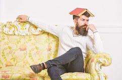 Macho sitter med den öppna boken på huvudet, som taket Tråkigt litteraturbegrepp Borrad grabb, matat upp av att läsa den gamla bo arkivbilder