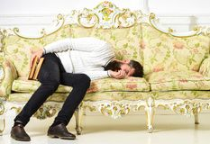 Macho sleep with book in hand. Boring literature concept. Man with beard and mustache lay on baroque style sofa, holds. Book, white wall background. Guy fall stock photography