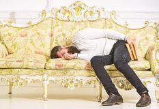 Macho sleep with book in hand. Boring literature concept. Man with beard and mustache lay on baroque style sofa, holds. Book, white wall background. Guy fall stock photo