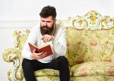 Macho sur le livre de lecture concentré de visage Concept scandaleux de best-seller Livre de lecture de type avec l'attention Hom image stock