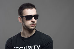 Macho tough security agent wearing sunglasses looking away at copyspace Stock Photos