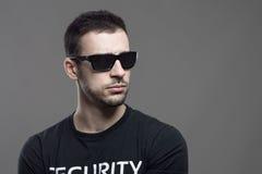 Macho twardy agent ochrony jest ubranym okulary przeciwsłonecznych patrzeje daleko od przy copyspace Zdjęcia Stock