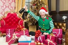 Macho w elfa kostiumowym uśmiechu z szampańską butelką Obrazy Stock