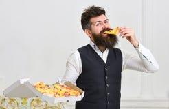 Macho w klasyków ubraniach głodnych, chwytów serowa pizza plasterek, je, biały tło Mężczyzna z brody i wąsy chwytami Fotografia Stock