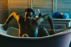 Macho z silnych ręk siedzieć nagi w wannie obrazy royalty free