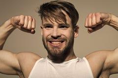 Macholächeln mit den starken Armen im weißen Unterhemd lizenzfreies stockfoto