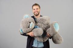 Macholächeln mit grauem Teddybären Großes Tierspielzeug des glücklichen Mannes Mannlächeln mit großem Tierspielzeug Geschenk und  lizenzfreie stockfotografie