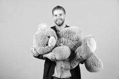 Macholächeln mit grauem Teddybären Großes Tierspielzeug des glücklichen Mannes Mannlächeln mit großem Tierspielzeug Geschenk und  stockfotos