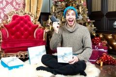Macholächeln mit Handy an Weihnachtsbaum Stockfotografie