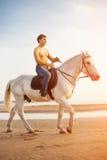 Machomann und Pferd auf dem Hintergrund des Himmels und des Wassers Jungenmodus lizenzfreies stockfoto
