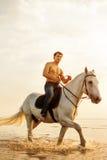 Machomann und Pferd auf dem Hintergrund des Himmels und des Wassers Jungenmodus stockbild