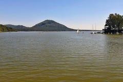 Machovo jezero,捷克共和国-威严19日2012年:Machovo有小船和Borny小山的jezero湖在夏天下午的背景 库存照片