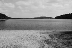 Machovo jezero lake with Bezdez castle on background and sand beach in foreground in Machuv kraj tourist area in czech republic w. Ith black and white royalty free stock image