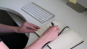 Macht Anmerkungen in einem Notizbuch auf einer weißen Tabelle Nahaufnahme stock video footage