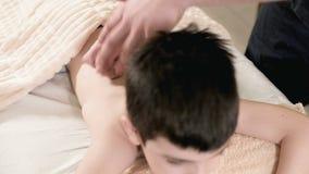 Macht männlicher Physiotherapeutenmasseur der Nahaufnahme einem kleinen Jungen eine Entspannungsmassage der Heilung, der auf eine stock video footage
