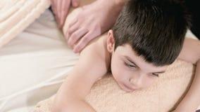 Macht m?nnlicher Physiotherapeutenmasseur der Nahaufnahme einem kleinen Jungen eine Entspannungsmassage der Heilung, der auf eine stock video