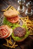 Machte geschmackvolles gegrilltes Haus zwei Burger mit Rindfleisch, Tomate, Zwiebel und Kopfsalat stockfoto