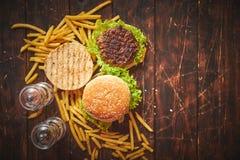 Machte geschmackvolles gegrilltes Haus zwei Burger mit Rindfleisch, Tomate, Zwiebel und Kopfsalat stockfotos
