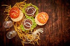 Machte geschmackvolles gegrilltes Haus zwei Burger mit Rindfleisch, Tomate, Zwiebel und Kopfsalat lizenzfreies stockfoto