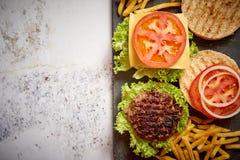 Machte geschmackvolles gegrilltes Haus zwei Burger mit Rindfleisch, Tomate, Zwiebel und Kopfsalat lizenzfreie stockfotografie