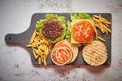 Machte geschmackvolles gegrilltes Haus zwei Burger mit Rindfleisch, Tomate, Zwiebel und Kopfsalat stockbilder
