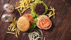 Machte geschmackvolles gegrilltes Haus zwei Burger mit Rindfleisch, Tomate, Zwiebel und Kopfsalat stock video