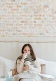Machtlose Frau, die unter Grippe im Schlafzimmer leidet Lizenzfreies Stockbild