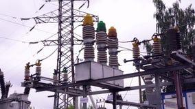Machtslijnen en elektrische polen Kader Lijnen met hoog voltage tegen achtergrond van elektrodistributieposten stock footage