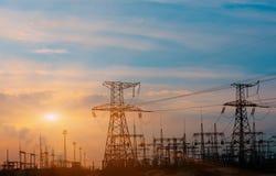 Machtslijnen met hoog voltage bij zonsondergang De post van de elektriciteitsdistributie Toren van de hoogspannings de Elektrisch stock foto