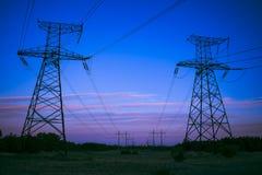 Machtslijnen met hoog voltage bij zonsondergang sta van de elektriciteitsdistributie stock foto's