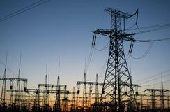 Machtslijnen met hoog voltage bij zonsondergang sta van de elektriciteitsdistributie royalty-vrije stock afbeeldingen