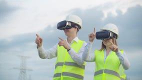 Machtslijnen met hoog voltage onder de controle van twee ingenieurs die virtuele werkelijkheid gebruiken om macht te controleren  stock videobeelden
