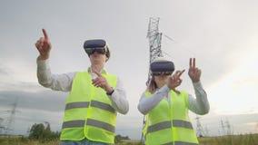 Machtslijnen met hoog voltage onder de controle van twee ingenieurs die virtuele werkelijkheid gebruiken om macht te controleren  stock video