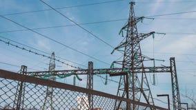 Machtspylonen met hoog voltage achter de hulpkantooromheining Omheining van het elektrohulpkantoor De energieindustrie vernieuwba stock footage