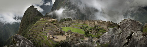 Machu Picchu. A fortress city of the ancient Incas, in a high saddle between two peaks, a panoramic showing the whole site and the clouded rocks stock photo