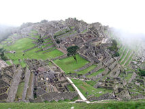 Machu Picchu from above. Looking down onto Machu PIcchu with mist and clouds rolling by. Peru royalty free stock image